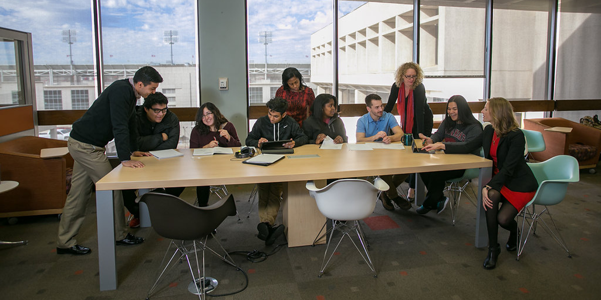 A group of students and staff have a discussion around a table.